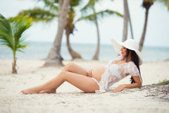 Beautiful pregnant woman lying on  sandy beach with palm trees Royalty Free Stock Images