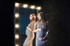 The beautiful pregnant woman in mirror reflection. Hands of the woman lie on a stomach Stock Image