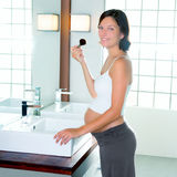 Beautiful pregnant woman on modern bathroom makeup. With brush in mirror royalty free stock photo