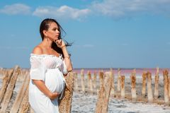 Beautiful pregnant woman in nature in white dress royalty free stock photography