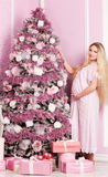 Beautiful pregnant woman. Near the Christmas tree royalty free stock image