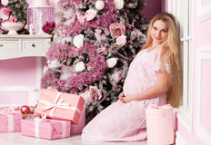 Beautiful pregnant woman. Near the Christmas tree stock image