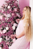 Beautiful pregnant woman. Near the Christmas tree stock photo