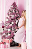 Beautiful pregnant woman. Near the Christmas tree royalty free stock photo