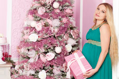 Beautiful pregnant woman. Near the Christmas tree stock images