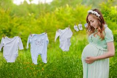 Beautiful pregnant woman outdoor hanging childrens clothes. Great time Royalty Free Stock Photo