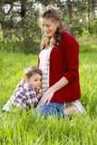 Beautiful pregnant woman outdoor with her little boy Royalty Free Stock Photos