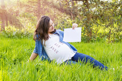 Beautiful pregnant woman outdoor with a paper in hand Stock Photography