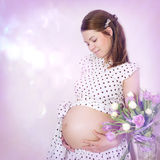 Beautiful pregnant woman portrait with tulips. Stock Photo