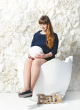 Beautiful pregnant woman posing with big egg at studio Stock Images