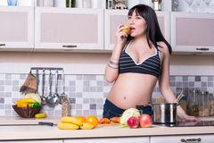 Beautiful pregnant woman prepares food Royalty Free Stock Image