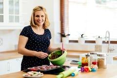 Beautiful pregnant woman preparing muffins Stock Photos