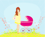 Beautiful pregnant woman pushing a stroller Royalty Free Stock Photo