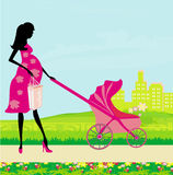 Beautiful pregnant woman pushing a stroller Royalty Free Stock Photos