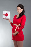 Beautiful pregnant woman in red dress with gift box over grey ba. Young beautiful pregnant woman in red dress with gift box over grey background royalty free stock images