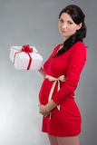Beautiful pregnant woman in red dress with gift over grey backgr Royalty Free Stock Photography