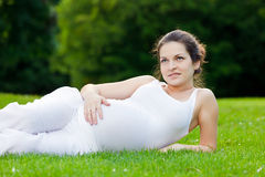 Beautiful pregnant woman relaxing. In the park Stock Images