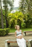 Beautiful pregnant woman relaxing on the bench Stock Photo