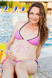 Beautiful pregnant woman relaxing near blue pool Stock Photo