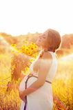 Beautiful pregnant woman relaxing in the park. Beautiful pregnant woman relaxing outside in the park Stock Photo