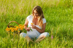 Beautiful pregnant woman relaxing in the park. Beautiful pregnant woman relaxing outside in the park Stock Photos