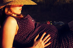 Beautiful pregnant woman relaxing in the park. Pregnant woman in hat resting Stock Photos