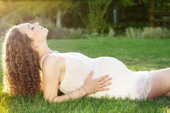 Beautiful pregnant woman relaxing in the park. Beautiful pregnant woman lying on the green lawn in park Stock Photography