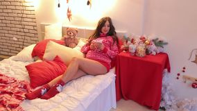 Pregnant woman is drinking tea near Christmas tree. Beautiful pregnant woman is resting on the bed with a cup of tea during the New Year holidays stock video