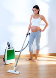 Beautiful pregnant woman retro vacuum housewife Stock Image