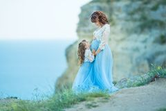 Beautiful Pregnant Woman in romantic flying dress at sea with daughter near ancient ruins of Greece city Gorgeous pregnant girl in stock image