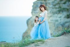 Beautiful Pregnant Woman in romantic flying dress at sea with daughter near ancient ruins of Greece city Gorgeous pregnant girl in stock photography