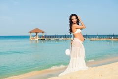Beautiful pregnant woman on a sandy beach. Dominican Republic, the Caribbean Sea. Stock Photos