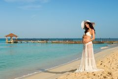 Beautiful pregnant woman on a sandy beach hugging her tummy. Dominican Republic, the Caribbean Sea. Royalty Free Stock Photography