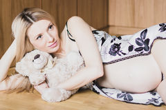 Beautiful pregnant woman in sexy nightwear lying down with teddy bear Royalty Free Stock Photo