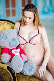Beautiful pregnant woman in sexy nightwear sitting on armchair with teddy bear. pregnant woman in cream lingerie with Stock Image