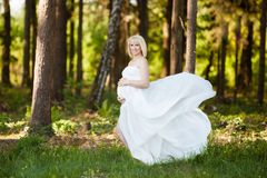 Beautiful pregnant woman in sheer long white maternity dress floating in the wind looking straight in the camera and smiling stock photos