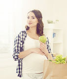Beautiful pregnant woman with shopping bags in kitchen. Motherho Stock Photography