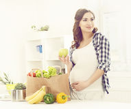 Beautiful pregnant woman with shopping bags in kitchen. Motherho. Od, pregnancy, maternity concept Stock Photos