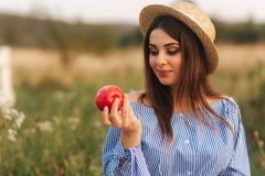 Beautiful pregnant woman show and eat red apple. Healthy food. Fresh fruits. Happy woman smile.  stock photography
