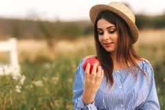 Beautiful pregnant woman show and eat red apple. Healthy food. Fresh fruits. Happy woman smile.  royalty free stock images