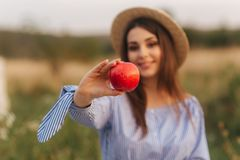 Beautiful pregnant woman show and eat red apple. Healthy food. Fresh fruits. Happy woman smile.  stock photos