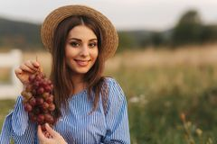 Beautiful pregnant woman show and eat red grapes. Healthy food. Fresh fruits. Happy woman smile.  royalty free stock photo