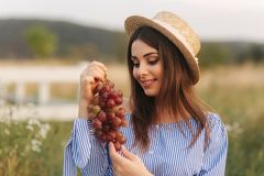 Beautiful pregnant woman show and eat red grapes. Healthy food. Fresh fruits. Happy woman smile.  stock photo