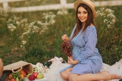Beautiful pregnant woman show and eat red grapes. Healthy food. Fresh fruits. Happy woman smile.  stock photography