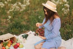 Beautiful pregnant woman show and eat red grapes. Healthy food. Fresh fruits. Happy woman smile.  stock image