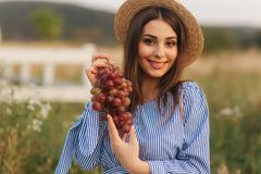 Beautiful pregnant woman show and eat red grapes. Healthy food. Fresh fruits. Happy woman smile.  royalty free stock photography