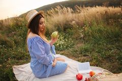 Beautiful pregnant woman show and eat red pear. Healthy food. Fresh fruits. Happy woman smile.  stock images
