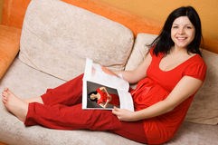 Beautiful pregnant woman sitting on the couch Royalty Free Stock Photo