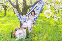 Beautiful pregnant woman sitting in hammock in blooming garden Royalty Free Stock Photography