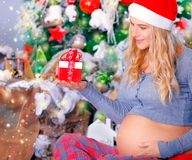 Pregnant woman with Christmas gift Stock Photos